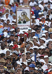 A man holds a sign mentioning Florida as he waits for Pope Benedict XVI to celebrate Mass at Antonio Maceo Revolution Square in Santiago de Cuba, Cuba, March 26, 2012. Pope Francis will visit Cuba later this month. (CNS photo/Paul Haring)
