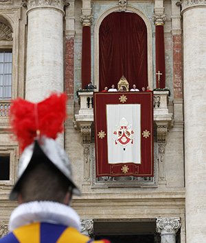 """A Swiss Guard is seen as Pope Benedict XVI delivers his Christmas message """"urbi et orbi"""" (to the city and the world) from the central balcony of St. Peter's Basilica at the Vatican Dec. 25. (CNS photo/Paul Haring) (Dec. 25, 2012) See POPE-CHRISTMAS to come."""
