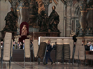 A worker carries chairs inside Saint Peter's Basilica during the preparations for the election of the new Pope at the Vatican