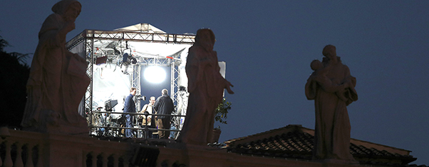 Television crew works in tent overlooking colonnade at Vatican