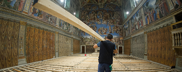 Worker carries in timber as Sistine Chapel is prepared for conclave