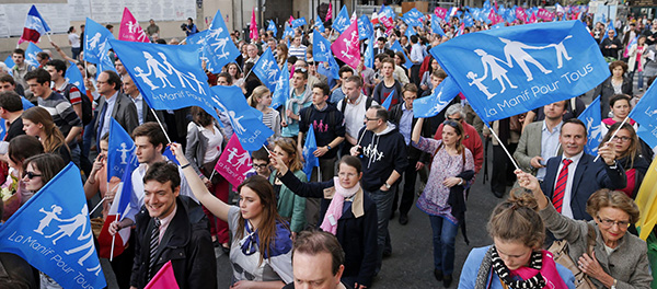 People wave banners during demonstration against France's planned legalization of same-sex marriage in Paris