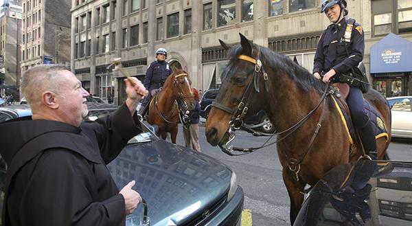 PRIEST BLESSES NEW YORK CITY POLICE OFFICER'S HORSE