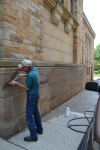 Friend of St. William John Wira attempts to clean spray paint off the walls of St. William in Price Hill after the church was defaced by vandals. (CT Photo/Megan Walsh)