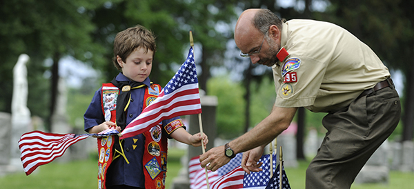 Young Boy Scout and Scoutmaster place U.S. flags at graves of military veterans