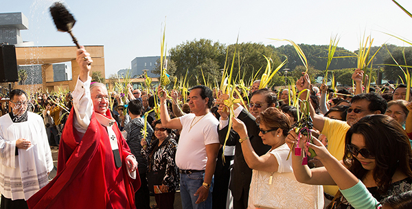 Archbishop Gomez blesses people holding palms with holy water during Palm Sunday Mass outside Los Angeles cathedral
