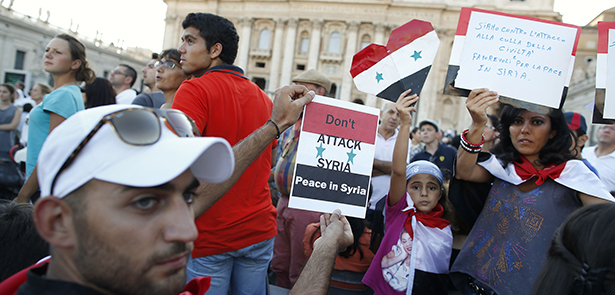 People from Syria hold up signs before pope leads prayer vigil for peace