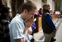 A young man kneels in prayer during the opening Mass of the National Prayer Vigil for Life at the Basilica of the National Shrine of the Immaculate Conception in Washington Jan. 21. The all-night vigil is held before the annual March for Life, which this year marked the 41st anniversary of the Supreme Court's Roe v. Wade decision that legalized abortion across the nation. (CNS photo/Tyler Orsburn) (Jan. 22, 2014) See VIGIL-OMALLEY Jan. 22, 2014.