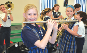 Sidney Stigler (with flute) and other St. Ignatius students get their first look at some of the instruments recently donated to the music program. (CT Photo/John Stegeman)