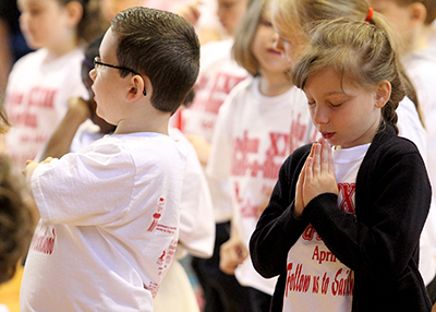 Jocelyn Brenot, 6, prays during Mass at John XXIII Catholic Elementary in Middletown Friday, April 25, 2014. The school held a special Mass to recognize the upcoming canonization of the school's namesake, Pope John Paul XXIII.