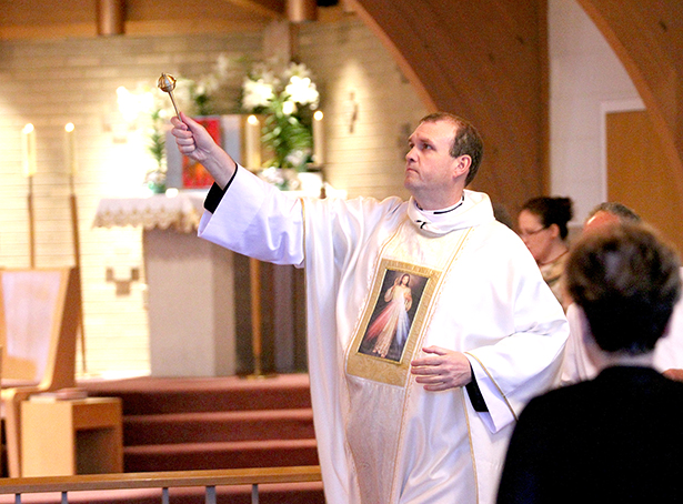 Father Eric Bowman sprinkles Holy Water while blessing the congregation during the special Mass at St. Adalbert Parish in Dayton Sunday, April 27, 2014, to celebrate the Canonizations of Pope John Paul II and Pope John XXIII. (CT Photo/E.L. Hubbard)