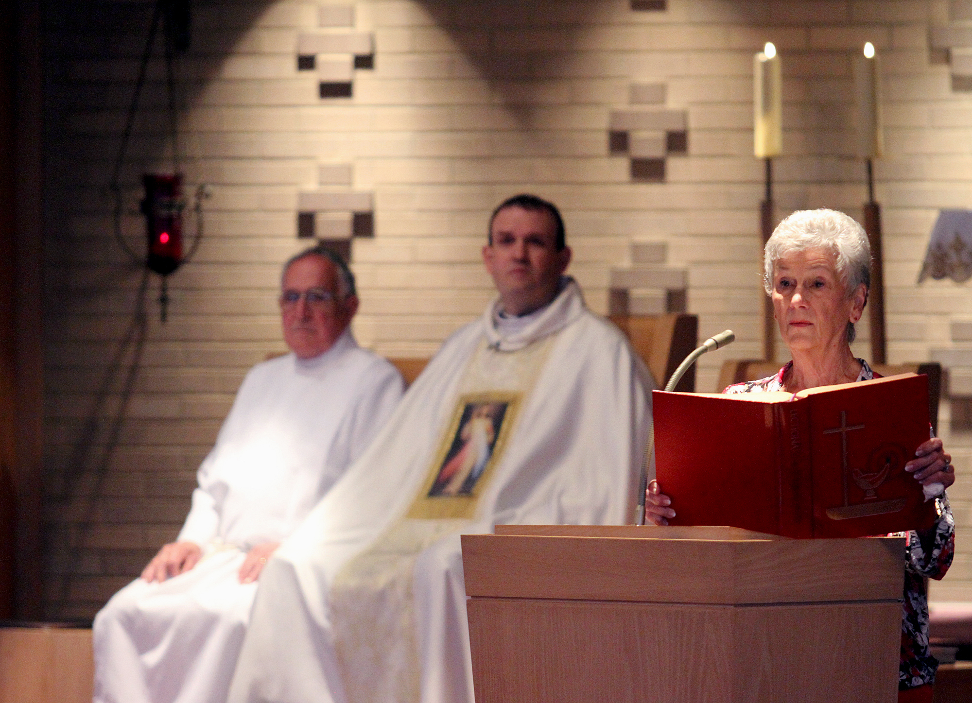 Lector Aggie Marcellino gives a reading during the special Mass at St. Adalbert Parish in Dayton Sunday, April 27, 2014, to celebrate the Canonizations of Pope John Paul II and Pope John XXIII. Listening are Ed Koth and Father Eric Bowman. (CT Photo/E.L. Hubbard)