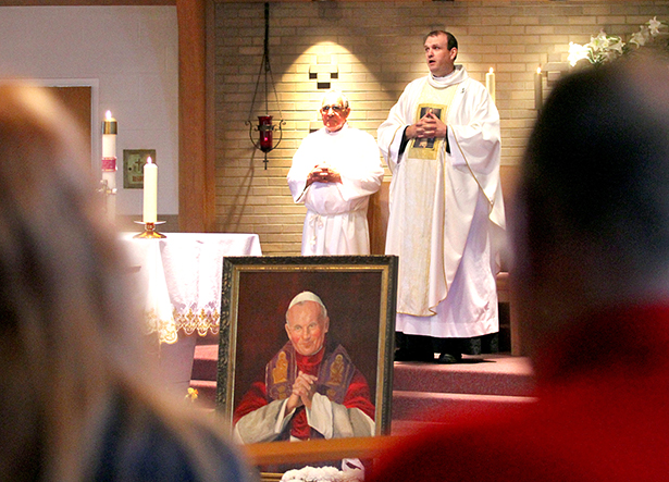 A framed portrait of Pope John Paul II sits in front of the altar as Father Eric Bowman gives the closing blessing during the special Mass at St. Adalbert Parish in Dayton Sunday, April 27, 2014, to celebrate the Canonizations of Pope John Paul II and Pope John XXIII. (CT Photo/E.L. Hubbard)