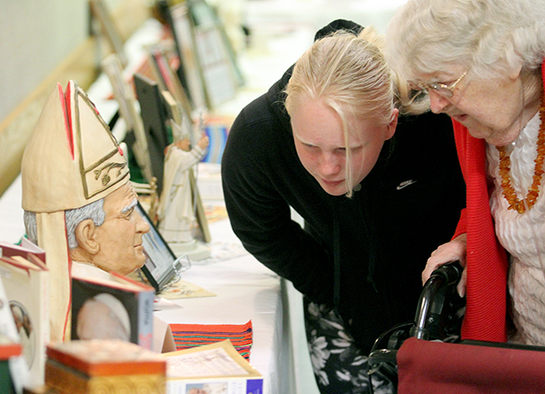 Eleanor Beringer, 11, and her grandmother, Florentine Brzozowski, examine the display featuring Pope John Paul II at the Polish Club Hall in Dayton Sunday, April 27, 2014. Brunch was served in the hall after a special Mass at St. Adalbert Parish to celebrate the Canonizations of Pope John Paul II and Pope John XXIII.