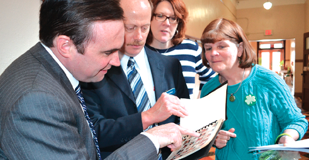 Cincinnati Mayor John Cranley, left, points out his picture in a St. William yearbook to school staff during his March 14 visit to the school.