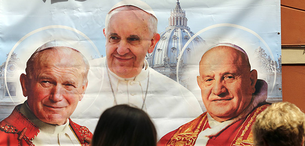 A woman takes a picture of an illustration depicting Blessed John Paul II, left, Pope Francis and Blessed John XXIII outside a shop in Rome April 23. On April 27, Pope Francis canonized both former popes. (CNS photo/Stefano Rellandini, Reuters)