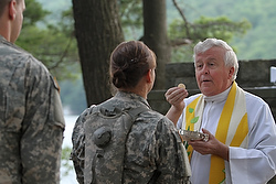 Augustinian Father Edson Wood, brigade chaplain at the U.S. Military Academy, distributes Communion during Mass at Camp Buckner in West Point, N.Y., in 2011. (CNS photo/Gregory A. Shemitz)