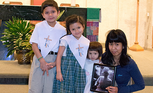 The Evans children, from left, Jimmy, Zoe, and Ashton, pose with their mother, Ao, holding a photo of her deceased husband Richard, after their baptism at St. James of the Valley Church in February. (Courtesy Photo)