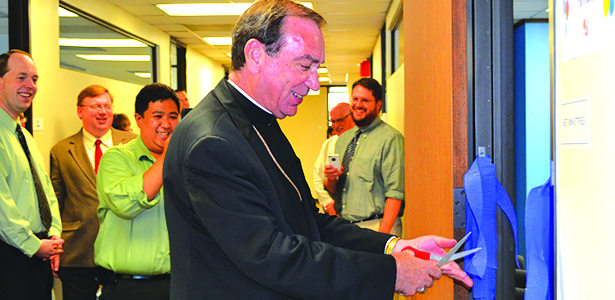 Archbishop Dennis M. Schnurr cuts a ribbon at a July 14 ceremonial opening of the NET Ministries regional office located in downtown Cincinnati while archdiocesan staff look on. The archbishop also read a prayer and blessed the new office. (CT Photo/John Stegeman)