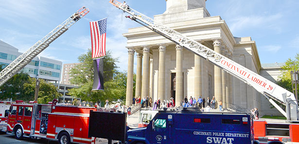 An American flag and a flag of mourning hang from between two Cincinnati Fire Department ladder trucks Sept. 14 before a Blue Mass celebrated at the Cathedral of St. Peter in Chains. A Cincinnati police SWAT vehicle is also visible. These vehicles, and others, were blessed prior to the Mass. (CT Photo/John Stegeman)