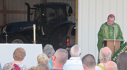 "Archbishop Dennis M. Schnurr speaks during a ""Farm Mass"" Sept. 5 in Adams County. A tractor can be seen in the background. (CT Photo/Paul Hannah)"