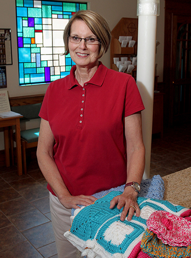 Linda Schaefer, at Our Lady of Sorrows Parish in Monroe, with some of the baby items she quilted for young mothers. (CT Photo/E.L. Hubbard)