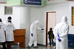 A Kenyan Port Health Services worker wearing full personal protective equipment commands a small boy, who is among nine Kenyans who were stranded in the Ebola-hit country Liberia, to return to an observation room for Ebola screening, as they arrive at Jomo Kenyatta International Airport Oct. 28 in Nairobi, Kenya. During his weekly general audience Oct. 29, Pope Francis urged prayers and international action to fight the Ebola virus. (CNS photo/Daniel Irungu, EPA) See POPE-EBOLA Oct. 29, 2014.