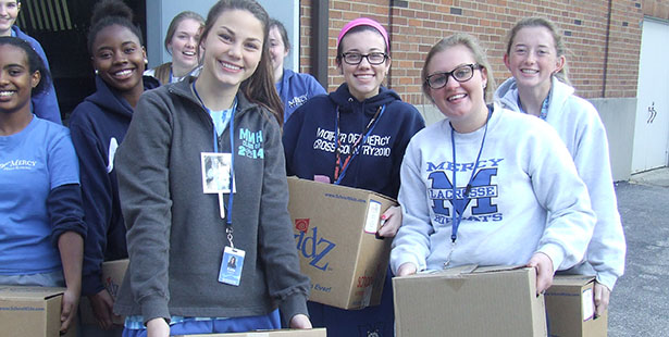 Mother of Mercy High School Students pose with canned goods collected for the needy. (Courtesy Photo/Mercy High School)