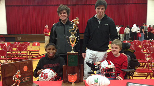 John Junker, left in back, and his brother Jake were counselors for Jacoby Gilliam, left in front, and Michael Overberg at Camp Campbell Gard this summer for the Muscular Dystrophy Association. The four are in back of La Salle's state Division II football championship trophy. (Courtesy Photo/La Salle High School)