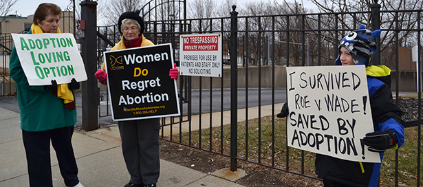 "Participants hold signs as part of the Cincinnati ""mini-March for Life."" (CT Photo/John Stegeman)"