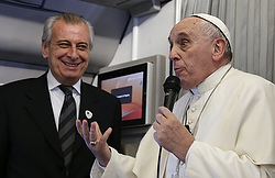 Pope Francis refers to Alberto Gasparri, left, papal trip planner, while answering a question from a French journalist aboard his flight to Manila, Philippines, Jan. 15. In response to the French reporter's question about freedom of religion and freedom of expression, the pope offered a hypothetical example of how Gasparri would receive a punch if he said a swear word against the pope's mother. (CNS photo/Paul Haring) See POPE-PRESS (UPDATED) Jan. 15, 2015.
