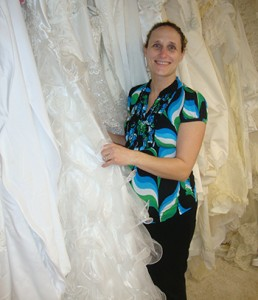 Cathy Diehl poses with wedding gowns that have been donated to her ministry. She makes burial garments for miscarried infants and babies that are stillborn or die at birth. (Courtesy Photo)