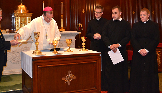 Archbishop of Cincinnati Dennis M. Schnurr blesses the chalices and pattens that will be presented to the ordinands prior to the May 16 ordination Mass. The ordinands, then deacons, Father Ethan Moore, Father Adrian Hilton and Father Eric Wood look on. (CT Photo/John Stegeman)