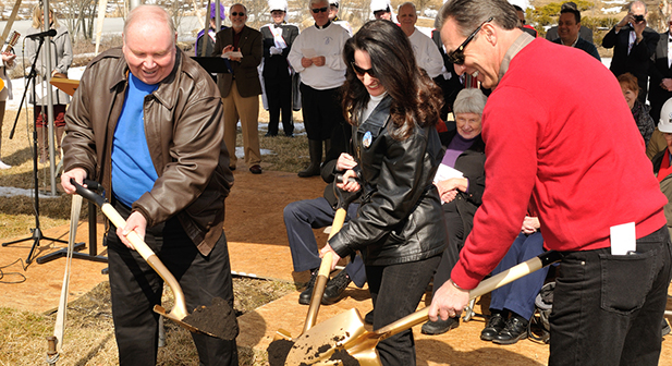 Father Jim Manning, along with JoAnn and Doyle Key, chairs of the building committee,  shovels the ceremonial dirt during the ceremony. (CT Photo/Jeff Unroe)