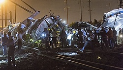 Rescue workers search for victims in the wreckage of a derailed Amtrak train in Philadelphia May 12. At least six people died and eight others were in critical condition as a result of the crash, a doctor from Temple University Hospital said the morning of May 13. (CNS photo/Bryan Woolston, Reuters)