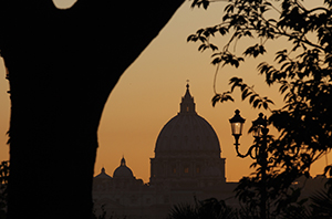 The dome of St. Peter's Basilica is seen through trees at sunset in a park near Villa Borghese in Rome Oct. 11. (CNS photo/Paul Haring)