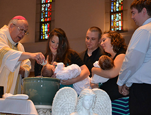 My sisters and their husbands look on as Bishop Joseph R. Binzer baptizes their daughters. (Courtesy Photo/John Stegeman)