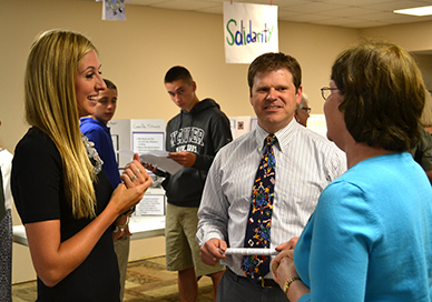 Sacred Heart of Jesus Catholic school elementary teachers Emily Owen, left, and Debbie Otero, right, speak with Tony Stieritz, director of the Archdiocese of Cincinnati Catholic Social Action Office at a June 3 event celebrating the students' capstone projects. (CT Photo/John Stegeman)