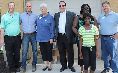 The Habitat for Humanity Team poses for a photo at the dedication: from left to right-- Bill Thoman, Plant Manager, St. Teresa of Avila; John McEwan, Field Operations Manager, HFHGC; Charmaine Kessinger, Director of Development, HFHGC; Rev. Michael Bidwell, Pastor, St. Teresa of Avila; Tennille Jones, Habitat Homeowner (and daughter); Ed Lee, CEO/President, HFHGC. (Courtesy Photo/Crystal McGrath)