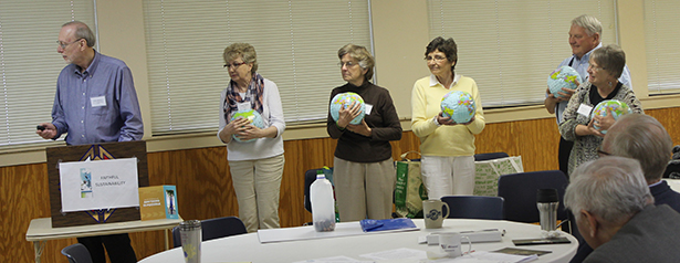 """James Heileman, Good Shepherd parishioner. leads a presentation on reducing our consumption.  Audience members are holding 5 """"earths,"""" the amount it would take to sustain the current world's population at U.S. consumption levels. (Courtesy Photo)"""