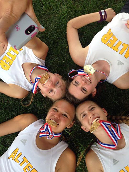 Kyly Borton, Kristen Petrovsky, Abby Nichols, and Perri Bockrath celebrate after winning a state championship in track. (Courtesy Photo/Alter High School)