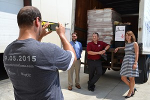 Sean Renyolds of the Archdiocese of Cincinnati takes a photo of the JTM Food Group donation. (CT Photo/John Stegeman)