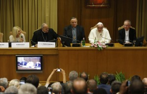 Pope Francis addresses a workshop on climate change and human trafficking attended by mayors from around the world in the synod hall at the Vatican July 21. Local government leaders were invited to the Vatican by the pontifical academies of sciences and social sciences to sign a declaration recognizing that climate change and extreme poverty are influenced by human activity. Also seen are, from left, Argentine model Valeria Mazza, serving as master of ceremonies; Bishop Marcelo Sanchez Sorondo, chancellor of the Pontifical Academy of Sciences; Cardinal Francesco Montenegro of Agrigento, Italy; and Cardinal Claudio Hummes, former prefect of the Congregation for the Clergy. (CNS photo/Paul Haring)