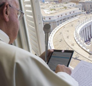 Pope Francis uses a tablet to officially open online registration for World Youth Day 2016 in Poland. He did this during the Angelus from the window of his studio overlooking St. Peter's Square at the Vatican July 26. (CNS photo/L'Osservatore Romano via EPA)