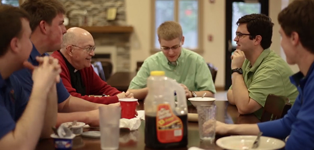 A screen capture from a new video released by the Vocations office shows young seminarians enjoying a meal with a priest.