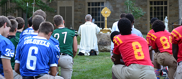 Players from Covington Catholic, Purcell Marian and Badin look on as Father Benedict Benedict O'Cinneslaigh, seminary rector, incenses the Blessed Sacrament. The SportsLeader Rosary Rally was the third to take place in this archdiocese, and the second this year. More than 20 are planned around the nation. (CT Photo/John Stegeman)