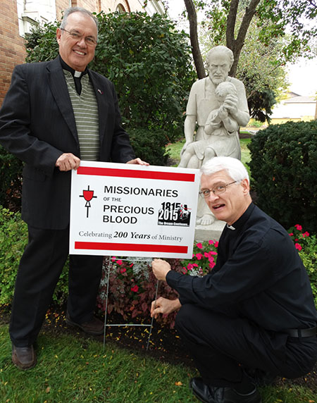 Precious Blood Fathers Angelo Anthony and Ken Pleiman put up a C.P.P.S. bicentennial sign outside of St. Joseph, one of the parishes where they minister in Dayton. (Courtesy Photo)