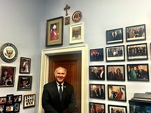"""Congressman Steve Chabot poses for a photo in front of the """"Pope Wall"""" in his Washington D.C. office. (CT Photo/Menachem Wecker)"""