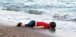Aylan Kurdit, a 3-year old migrant from Syria, who drowned in a failed attempt to sail to the Greek island of Kos, lies on the shore Sept. 2 in the Turkish coastal town of Bodrum. (CNS photo/Reuters)