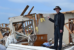 Bishop James V. Johnston Jr. of Springfield-Cape Girardeau, Mo., stands amid rubble near St. Mary's Catholic Church in Joplin May 24 after a monster tornado struck the city May 22, 2011. The church, rectory, school and parish hall were destroyed by the massive F5 tornado. (CNS photo/Emily Molinaro, The Mirror)